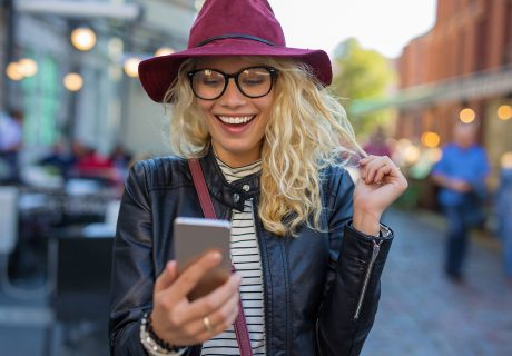 happy woman smiling at search results on smartphone